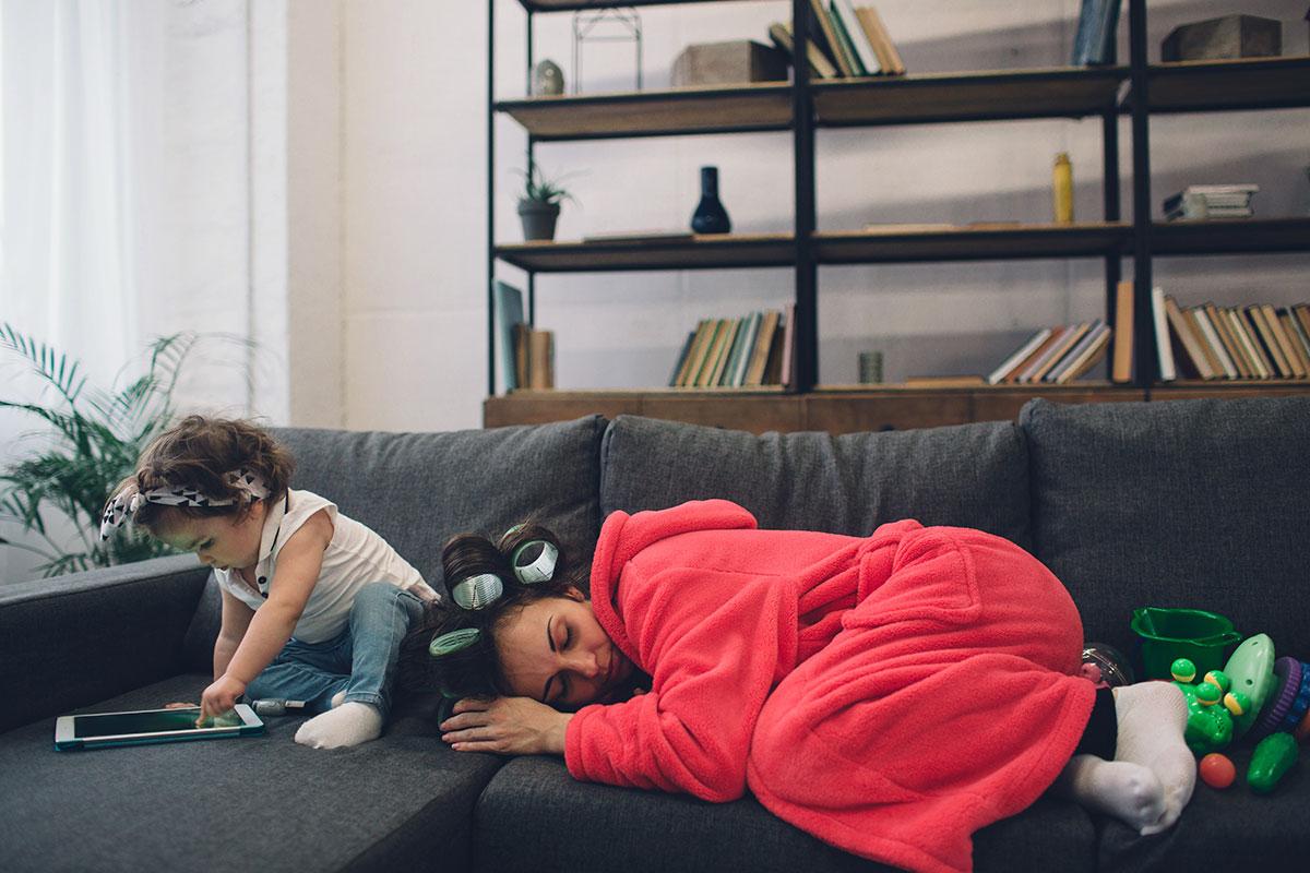 Mãe cansada deitada no sofá com sua filha brincando com um Tablet.