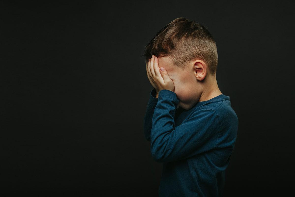 Abandono Afetivo. Imagem: Criança sozinha com as mãos cobrindo o rosto